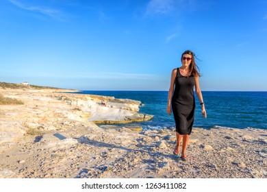 Brazilian brunette woman walking in the rocks in a beautiful beach landscape in Cyprus, Europe