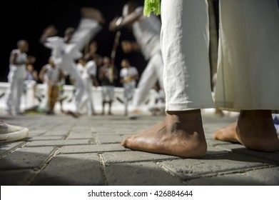 Brazilian capoeira group performing at night in Salvador, Bahia, Brazil with a focus on the feet of a performer in the foreground