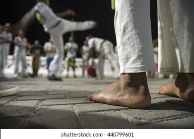 Brazilian capoeira group performing at night in Salvador, Bahia, Brazil. Focus on the feet in the foreground.