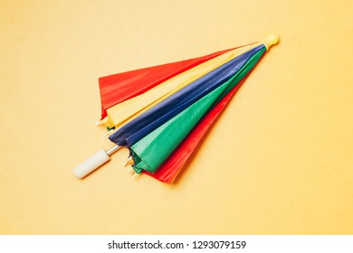 """Brazilian Carnival concept. Colorful """"Frevo"""" umbrella over yellow background."""