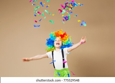 Brazilian Carnival. Happy clown boy with large colorful wig. Let's party! Funny kid clown. 1 April Fool's day concept. Portrait of a child throws up a multi-colored tinsel and confetti. Birthday boy.