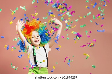 Brazilian Carnival. Venice Carnival. Little boy in clown wig jumping and having fun. Portrait of a child throws up a multi-colored tinsel and confetti. Birthday boy. Positive emotions.