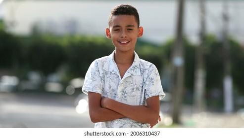 Brazilian child smiling at camera outside in street. Hispanic south american kid boy