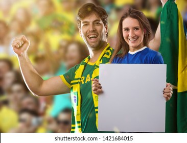 Brazilian couple holding white empty boards on a stadium on a soccer game, cheering for Brazil to be the champion.