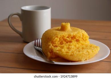 Brazilian Couscous (Cuscuz Brasileiro) and a cup of coffee on wooden background. Brazilian breakfast.