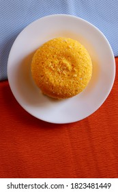 Brazilian Couscous (Cuscuz Brasileiro) on blue and orange background. Typical Northeast Brazilian dish. Vertical photo.