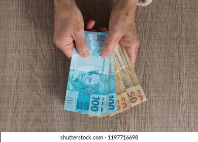 Brazilian currency, Money from Brazil. Overhead of senior person holding bills.