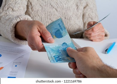Brazilian currency, Money from Brazil. Senior person making a loan to a young male at the office.