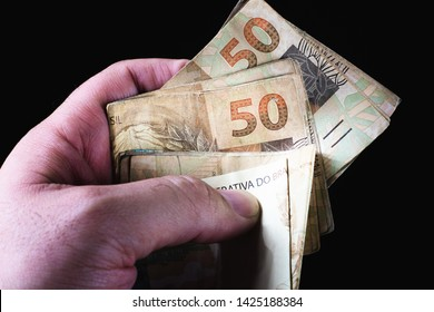 Brazilian currency.  Picture of man holding many 50 real notes with black background.