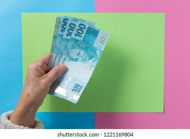 Brazilian currency: Real. Money from Brazil. Top view of old woman's hand handling bills.
