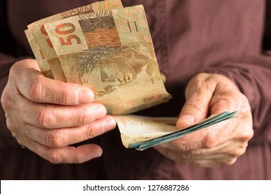Brazilian currency: Real. Money from Brazil. Front view senior person holding bills.