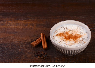 Brazilian dessert canjica of white corn with cinnamon in bowl. Selective focus. Copy space