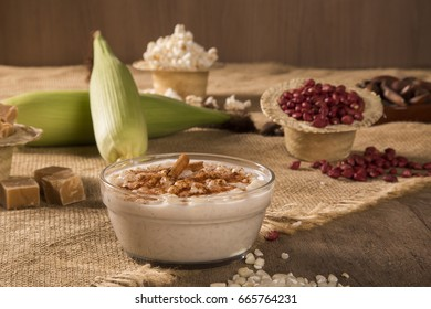 Brazilian dessert canjica of white corn with cinnamon in transparent plate.