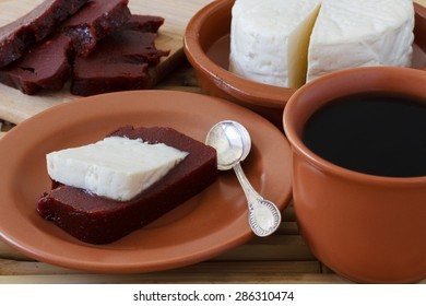 Brazilian dessert Romeo and Juliet, goiabada and Minas cheese with cup of coffee and fresh goiaba on wooden table. Selective focus