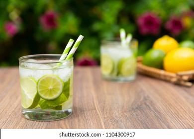 Brazilian drink Caipirinha with ingredients on wooden table and plants on the background