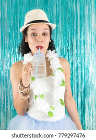 Brazilian is drinking a colorless drink. Water. Beautiful woman is in hat, white Hawaiian necklace and tutu skirt. Dressed for Carnival. Concept of party, New Year's Eve, Mardi Gras and Joy.