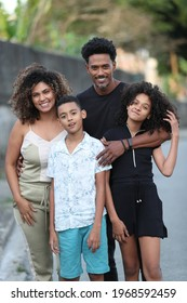 Brazilian family posing for photo looking at camera. Father, wife and children together