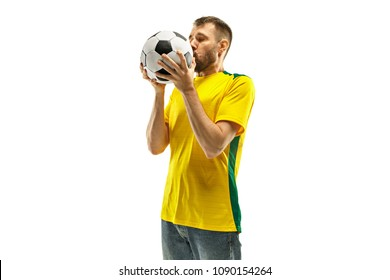 Brazilian fan celebrating on white background. The young man in soccer football uniform kissing ball at white studio. Fan, support concept. Human emotions concept.
