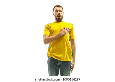 Brazilian fan celebrating on white background. The young man in soccer football uniform standing and singing a hymn at white studio. Fan, support concept. Human emotions concept.