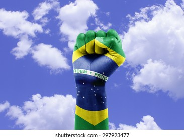Brazilian fan with hand raised on sky celebrating victory
