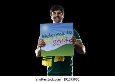 Brazilian Fan holding a welcome to Brazil sign, on a black background.