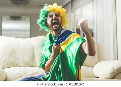 Brazilian fan watching a soccer match at home