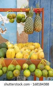 Brazilian farmers market featuring tropical fruits like pineapple, papaya, limes, and avocados
