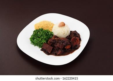 Brazilian Feijoada dish on brown background.