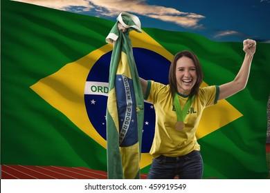 Brazilian female Athlete Winning a golden medal in front of a brazilian flag.