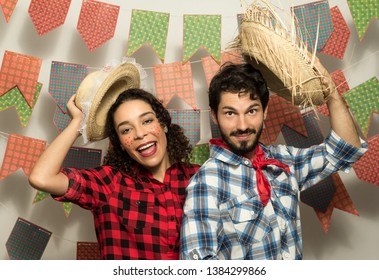 Brazilian Festa Junina. June party in Brazil. Couple wearing typical clothes is waving with the straw hat. They are inviting to the party, welcoming.