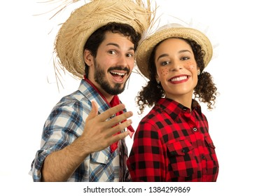 Brazilian Festa Junina. June party in Brazil. Beautiful couple wearing plaid clothes, traditional of the celebration. Man is inviting you to join in the party and the fun.