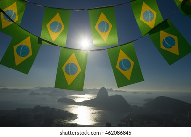 Brazilian flag bunting backlit above the city sunrise skyline view of Sugarloaf Mountain and Guanabara Bay