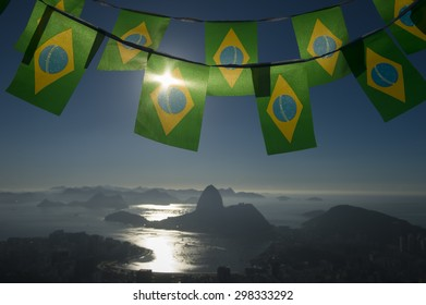Brazilian flag bunting hanging above the city sunrise skyline view of Sugarloaf Mountain and Guanabara Bay
