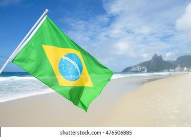 Brazilian flag flying in bright sun above the city skyline at Ipanema Beach in Rio de Janeiro, Brazil