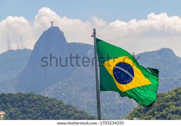 Brazilian flag with the image of the Redeemer Christ in the background in Rio de Janeiro, Brazil - March 15, 2020: Brazilian flag outdoors with the image of the Redeemer Christ  the background in Rio.