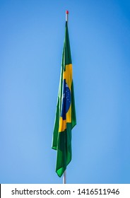 Brazilian flag on pole without wind in front of blue sky.