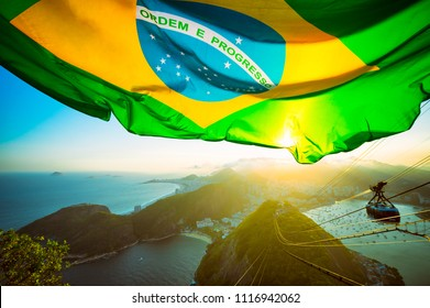 Brazilian flag shines above the golden sunset city skyline at Sugarloaf  Mountain in Rio de Janeiro Brazil. Translation: Order and Progress