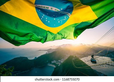 Brazilian flag shines above the golden sunset city skyline at Sugarloaf Pao de Acucar Mountain in Rio de Janeiro. Translation: Order and Progress