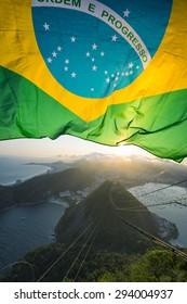 Brazilian flag shines above the golden sunset city skyline at Sugarloaf Mountain in Rio de Janeiro Brazil