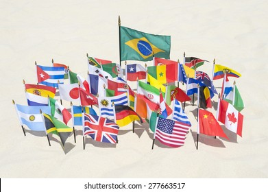 Brazilian flag surrounded by international flags flying on smooth sand beach in Rio de Janeiro Brazil