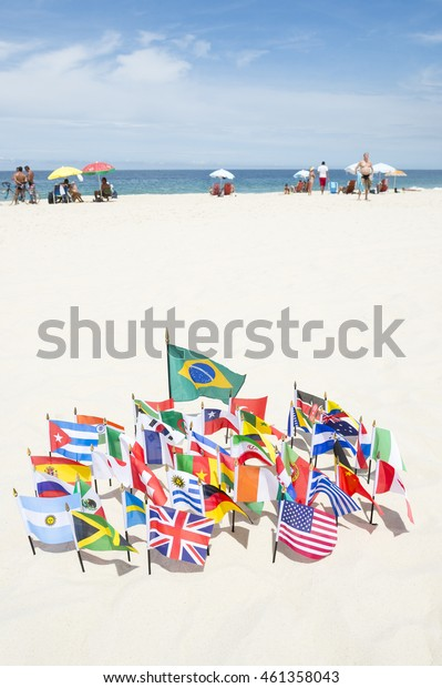 Brazilian flag surrounded by international flags flying on smooth sand at Ipanema Beach in Rio de Janeiro, Brazil
