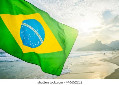Brazilian flag waving backlit in front of the sunset skyline at Ipanema Beach in Rio de Janeiro, Brazil