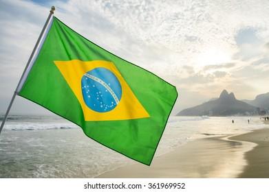Brazilian flag waving in front of the sunset skyline at Ipanema Beach in Rio de Janeiro, Brazil