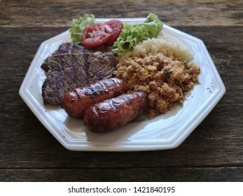 Brazilian food dish - Barbecue with beans, rice and salad.