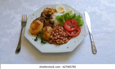 Brazilian food dish with fork and knife on white tablecloth