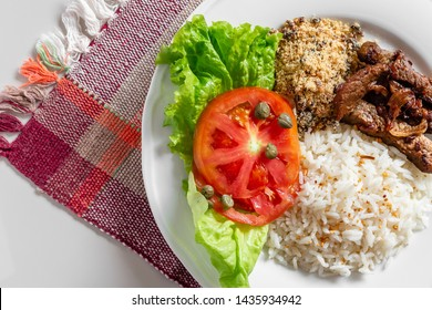 Brazilian food dish seen from the top on plaid cloth and white background
