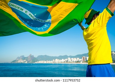 Brazilian football fan flying flag in front of Ipanema Beach city skyline Rio de Janeiro. Translation: Order and Progress