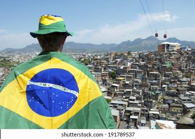 Brazilian football fan standing in Brazil flag in front of favela slum background in Rio de Janeiro