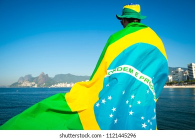Brazilian football fan wrapped in giant flag and hat in front of Ipanema Beach city skyline Rio de Janeiro. Translation: Order and Progress