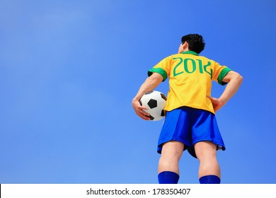Brazilian football player with 2014 shirt holding soccer ball with blue sky